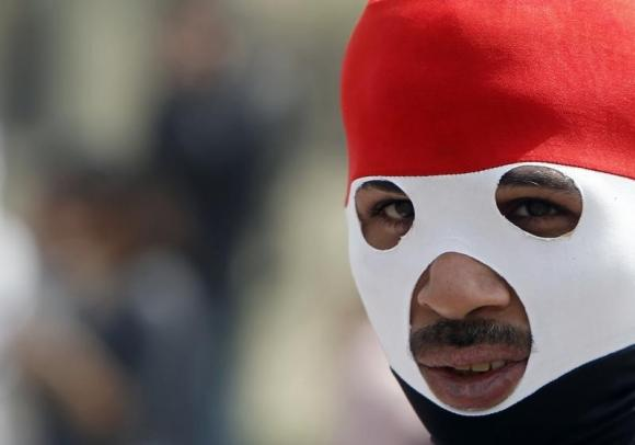 Protester wearing mask in the colours of the Egyptian flag is seen at Tahrir Square in Cairo